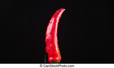 red hot pepper, close - up. Drops of water fall on a...