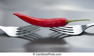 Red hot pepper on a gray plate. Spices and vegetables. Spicy foods and vitamins