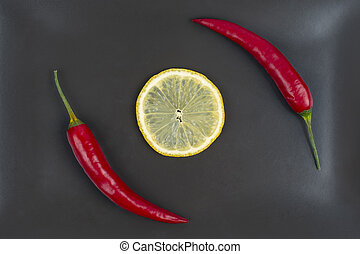 Red hot pepper with lemon on a gray plate. Healthy vegetable food and vitamins