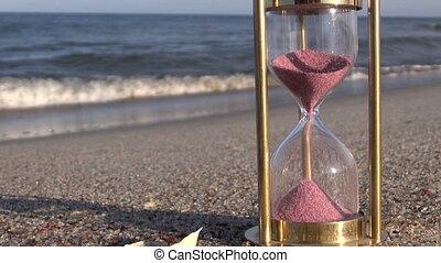 red hourglass on sea beach sand
