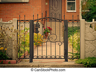 Red house facade with iron fence, green trees and flowers