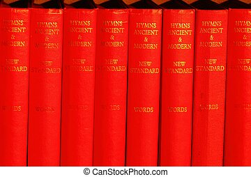 bright red hymn books lined up on a shelf