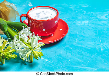 Red in white dotted cup of coffee and white hyacinths