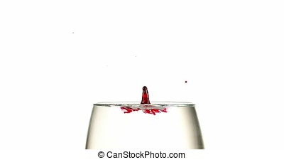 Red Ink falling into Liquid against White Background, Slow motion