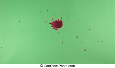 Red Ink Splatter Over Green Screen Background