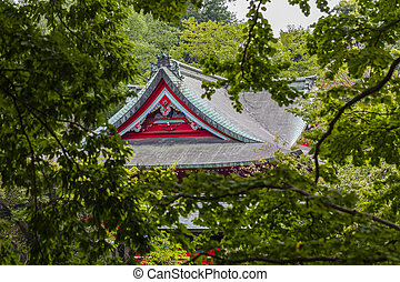 Red japanese temple among the trees in summer