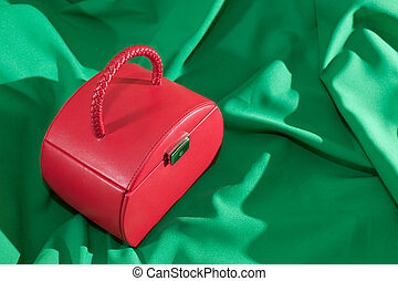 Red jewellery case on the green background