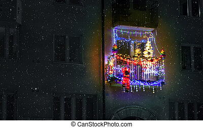 red jingle bells, lights, fir branches with ornaments on balcony in european city street