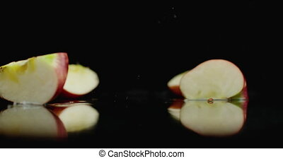 Red juicy sliced ??apple falling on a glass with splashes of water in slow motion on a dark background.