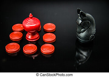 Red King chess in group of pawns challenge with Black Knight Thai chess piece on black background and selective focus