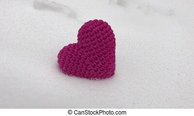 Red knitted heart lies on white snow