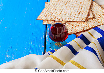 Red kosher wine with a white plate of matzah or matza and a...