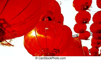 Red lanterns tassel swaying in wind, behind sun, elements of East, china new year.