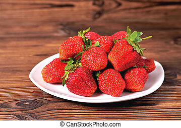 red large strawberries in a white plate on a natural brown background close-up