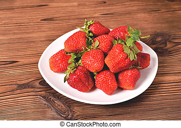 red large strawberries in a white plate on a natural brown background