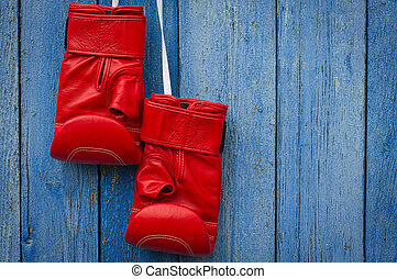 Red leather boxing gloves hanging on a rope
