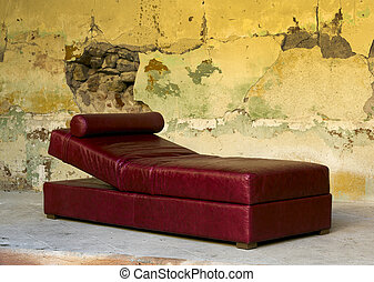 Red leather Chaise Longue against colorfull textured dilapidated wall