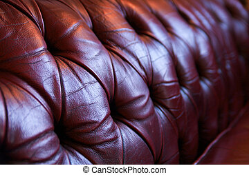 Red leather chesterfield sofa - Close-up of backrest of red...