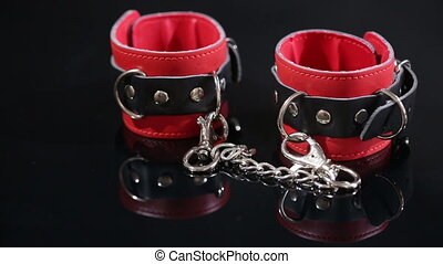 Red leather handcuffs in black background. sex toy