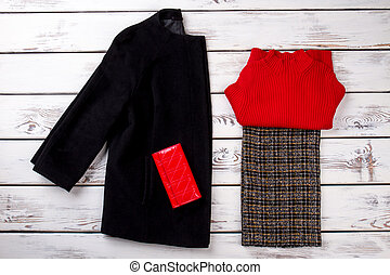 Red leather wallet on black cashmere coat.
