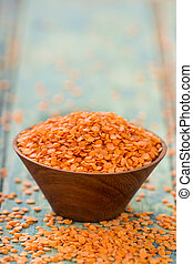 Red lentils in bowl on a blue wooden table