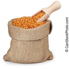 red lentils in burlap bag with wooden scoop