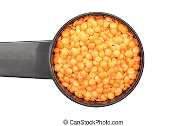 Red lentils on measuring spoon and white background