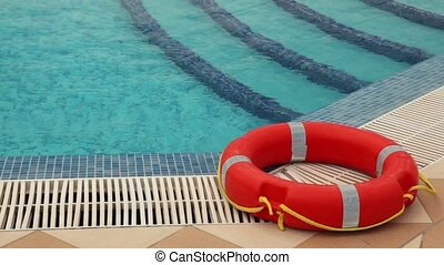 Red life buoy lies on the edge of the pool, the wavy surface...