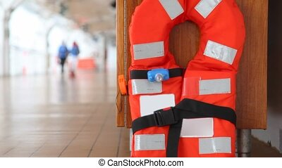 red life jacket on ship deck close up against walking people