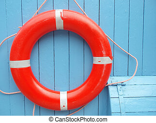 Red lifebuoy hanging on a clear blue wall