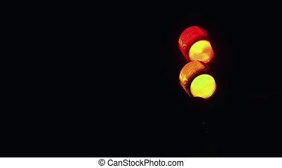 Red light for car traffic turns on in the darkness on the street.