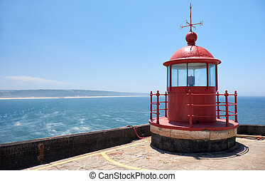 Red lighthouse lamp room on blue sky and sea background in Nazare, Portugal