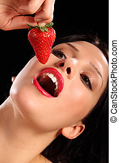 Red lips young woman eating fresh strawberry fruit