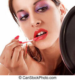 Red lipstick - Close-up of a womans lips applying red...