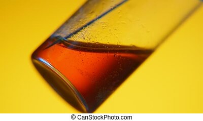 Red liquid is soaked into a syringe from a sample tube in a...