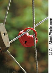 Red Lock in heart shape on rope bridge
