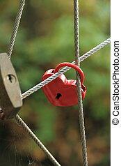 Red Lock in heart shape on rope bridge