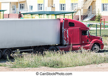 Red long-distance bonnet truck with a white semitrailer in the countryside