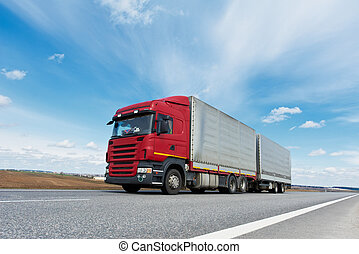 Red lorry with grey trailer over blue sky