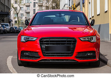 red luxury car parked on city