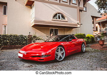 Red luxury sport car on the parking area in front of a house