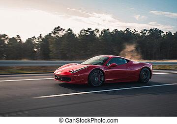 Red luxury sport sedan on the road