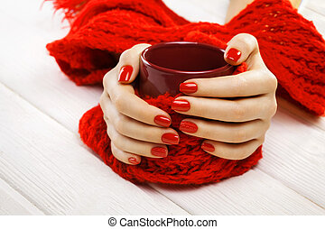 red manicure with a cup of tea
