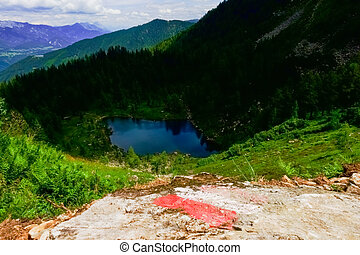 mark on a rock with view to a deep blue mountain lake