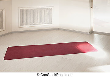 Red mat on an empty gym floor