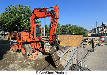Red mechanical digger in the city