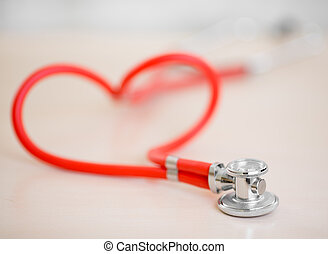 Red medical stethoscope in shape of heart on table