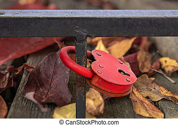 Red metal heart shape lock on an iron fence. Autumn background bright, colorful leaves. The sign of eternity.