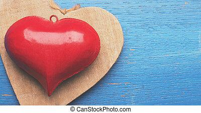 Red metal heart shape on blue wood