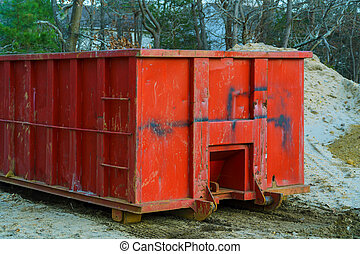 Red metal waste container with building debris